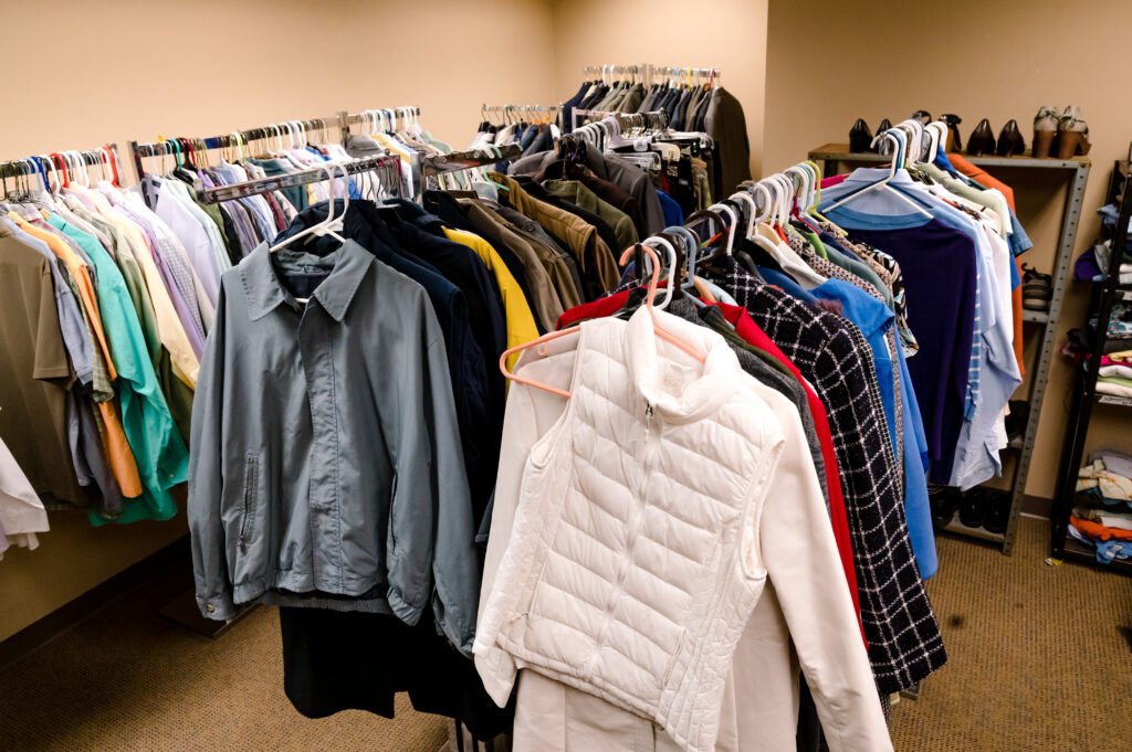 A closet of casual and professional clothes are hung on a series of clothing racks - as part of the Career Closet program