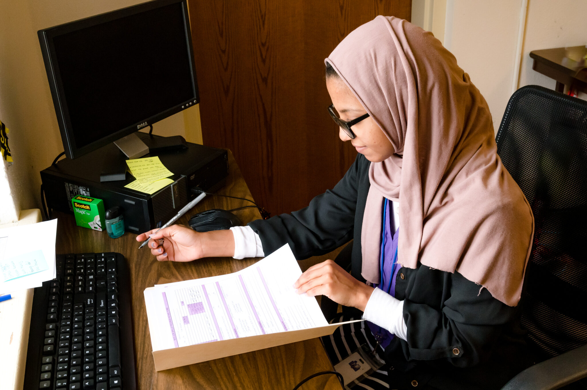 A young woman in a hijab and glasses reads a sheet of paper in front of her intently