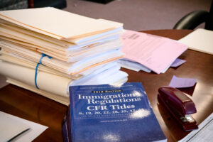 """A blue book titled """"Immigrations Regulations CFR Titles"""" sits at the front of a table, with a stack of manila folders and forms behind it. A maroon stapler sits to the right of the book."""