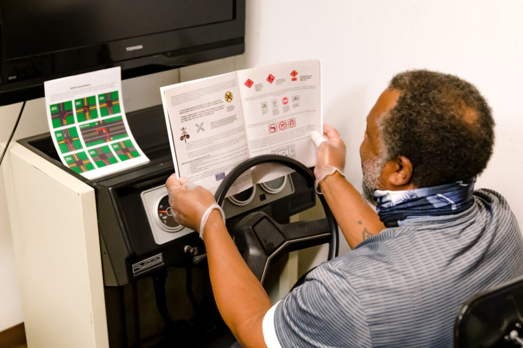 An elderly gentleman reviews a driver education program manual while in the seat of a driving simulator