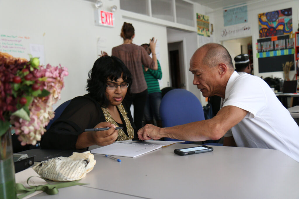 A young woman sits reading a sheet of paper, while an older gentleman reads on and points to her sheet as part of a learning program.